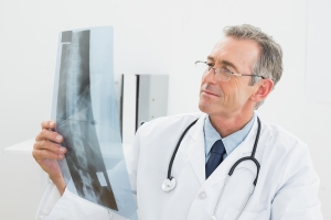 Concentrated male doctor looking at x-ray picture of spine in th